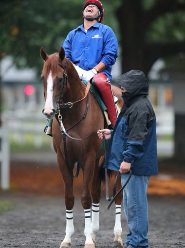 Exercise rider William Delgado, aboard California Chrome, shares a joke with assistant trainer Alan Sherman at Belmont Park Thursday morning before taking to the race track. June 5, 2014