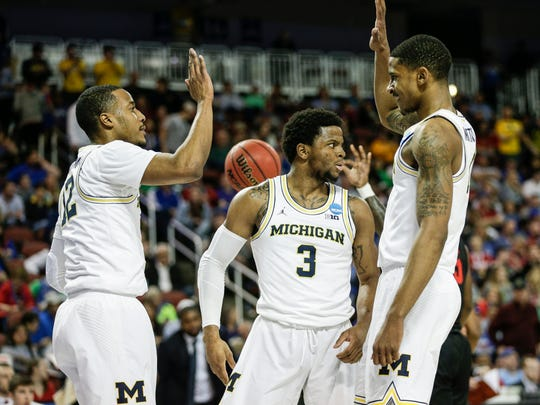 Michigan guard Muhammad-Ali Abdur-Rahkman (12), guard Zavier Simpson (3) and guard Charles Matthews (1)  celebrate a play against Houston during first half of second round of the NCAA tournament at INTRUST Bank Arena in Wichita, Kan., Saturday, March 17, 2018.