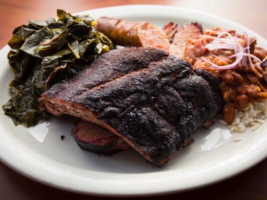 A three-meat platter with ribs, sausage, brisket, collard