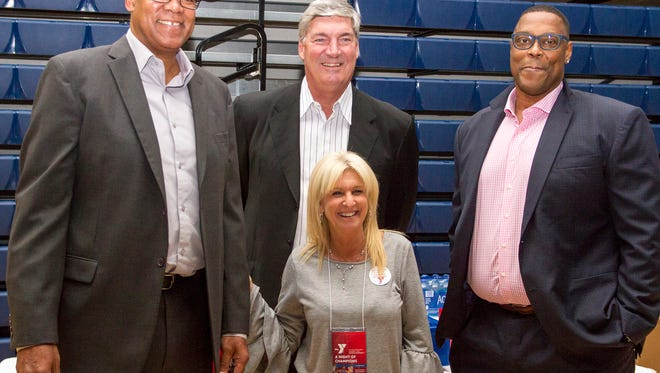 """Detroit Pistons """"Bad Boys"""" James Edwards, left, Bill Laimbeer, center, and Rick Mahorn pose for a photo with YMCA committee member LeeAnn Baker at the 2017 Night of Champions benefit for the YMCA of the Blue Water Area Oct. 26."""