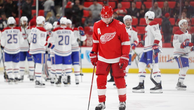 Detroit Red Wings left wing Justin Abdelkader (8) looks down as the Montreal Canadiens celebrate behind him after the game at Little Caesars Arena on April 5, 2018.