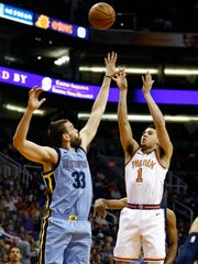 Back from injury, Phoenix Suns guard Devin Booker (1) shoots over Memphis Grizzlies center Marc Gasol (33) during the first half of an NBA basketball game, Tuesday, Dec. 26, 2017, in Phoenix. (AP Photo/Ross D. Franklin)