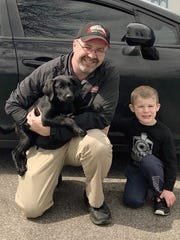 LaRosa's Pizzeria driver John Parrett reunites with kindergartner Jimmy Miller's and the child's dog Chili in Independence April 6. Parrett found the puppy while delivering a pizza to the Miller family in Independence.