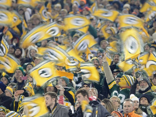 Getting fans whipped up at the right time is a key component of the game-day experience at Lambeau. Here fans wave flags during the Nov. 9 game against the Chicago Bears.