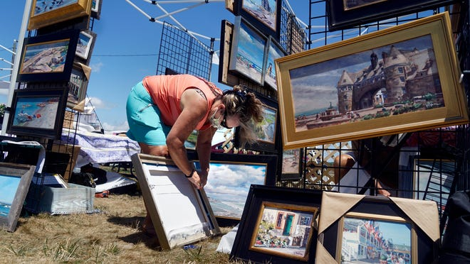 Artist Pati Sylvia rearranges some of her collection of oil paintings at her tent on Sunday afternoon at the Narragansett Fine Art and Craft Show. The outdoor event observed crowd limits and asked visitors to wear face mask and was hosted by the Narragansett Chamber of Commerce, PVD Artisans Market and Bryce Studio.