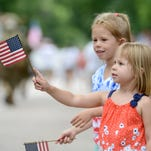Grace Brown, of Fort Collins, waves her American flag during the Independence Day parade along Mountain Avenue in Fort Collins in 2014.