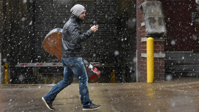 A musician does a FaceTime chat as he walks to show the snow that just arrived as he carries his guitar back to his car Friday Jan. 12, 2018, in Nashville, Tenn