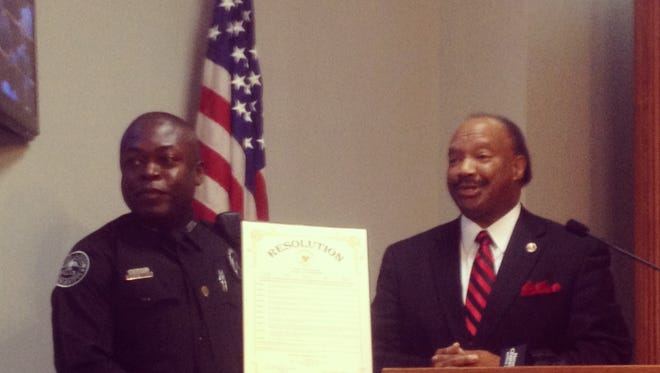 """Hinds County Supervisor Robert Graham (right) honors Jackson police officer James Edwards with a resolution and """"Above and Beyond Award"""" for saving 11 people from a recent apartment fire."""