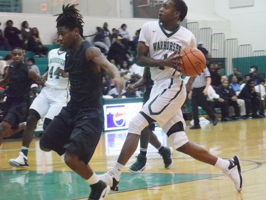 Peabody's Cedric Russell Jr. (1, right) drives to the basket against Rapides' Desmond Green (10, left).