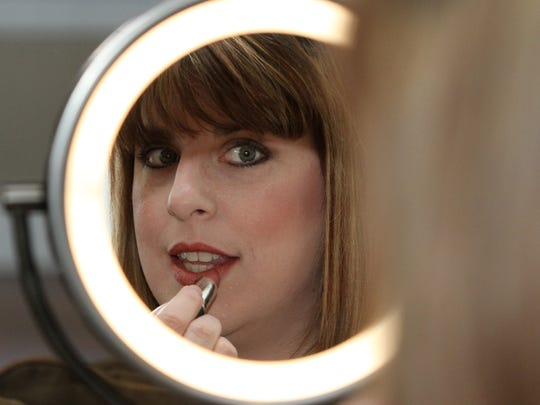 Noreen Diani, owner of The Organic Face, applies lipstick at her Manchester home.