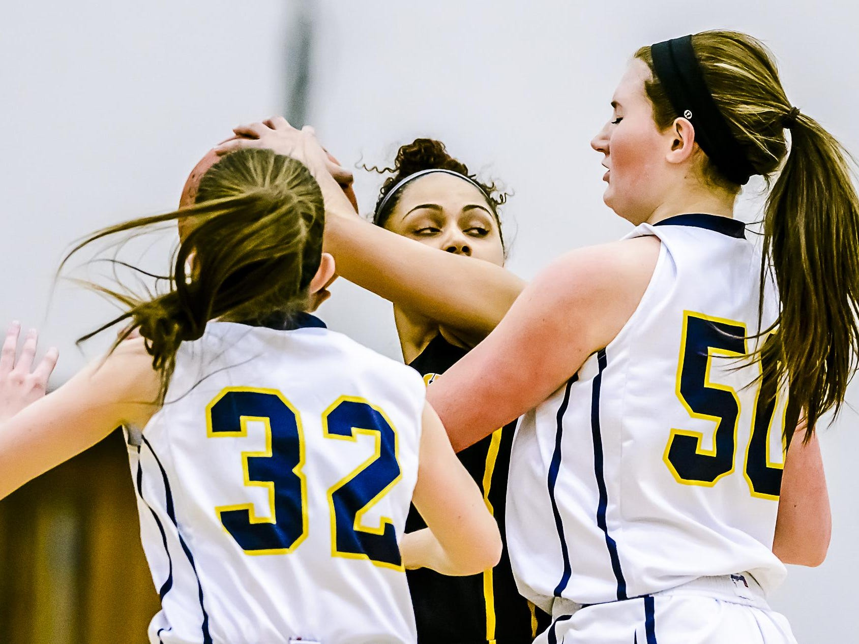 Mariyah Moore ,center, of Waverly looks to pass out of a double team trap by Jessah McManus ,32, and Gabby Iacobellis ,50, of DeWitt during their game Friday February 12, 2016 in DeWitt. KEVIN W. FOWLER PHOTO