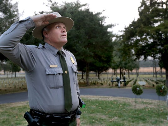 Jim Lewis, a park ranger at Stones River National Battlefield, salutes the American flag Friday, Dec. 19, 2014 at the National Cemetery before lowering it and taking the flag in for the night.