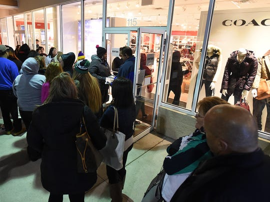 A crowd waits Friday morning at the Coach Store at Tanger Outlets in Rehoboth Beach.<137> and Lewes as thousands of shoppers have descended on the Outlet Centers to hunt for bargains and start their Holiday Shopping.<137>