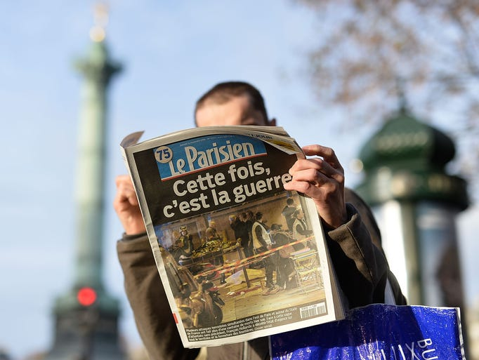 A man reads a French newspaper after a terrorist attack