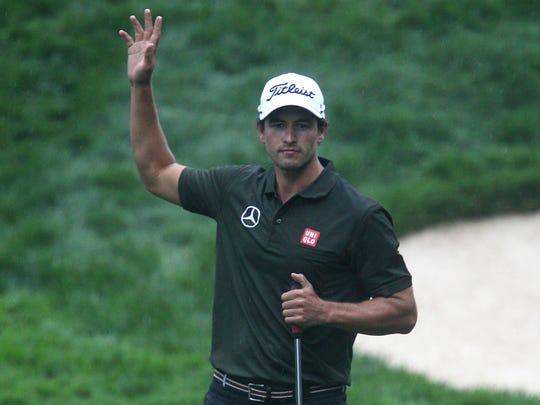Adam Scott waves after making a birdie putt on No. 13.