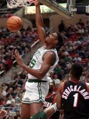 Boston Celtics' Acie Earl puts the ball away on a reverse dunk in front of Portland Trailblazers' Rod Strickland right in the first half of their NBA pre-season exhibition game in Hartford Conn. Thursday Oct. 20 1994. (AP Photo/Bob Child)