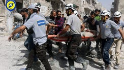 Rescue workers work the site of airstrikes in the al-Sakhour