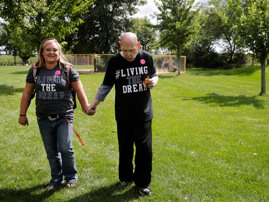 Emily Luebke, with Agape of Appleton, holds Phillip Fischer's hand as they make their way through Mulberry Lane Farms during Fischer's Live Your Dream day.