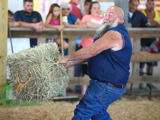 Participants try their best at the annual haybale-tossing