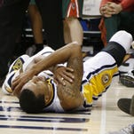 Feb 27, 2014; Indianapolis, IN, USA; Indiana Pacers guard George Hill (3) lays on the court after injuring his shoulder against the Milwaukee Bucks at Bankers Life Fieldhouse. The Pacers won 101-96. Mandatory  Credit: Brian Spurlock-USA TODAY Sports
