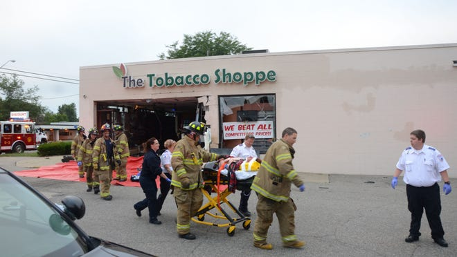 Injured driver Trevor P. Long is taken to an ambulance after crashing into The Tobacco Shoppe on Wednesday morning. Long was reported in critical condition after the crash.
