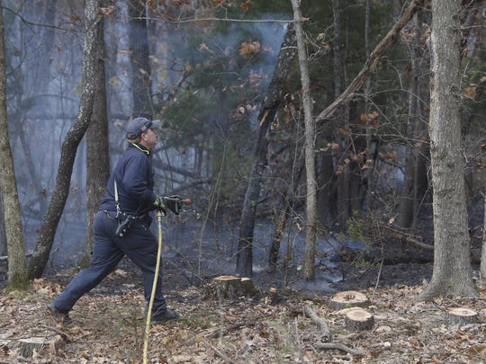 A firefighter battles a brush fire in the woods Tuesday just south of the Springfield Sanitary Landfill near Farm Road 34.