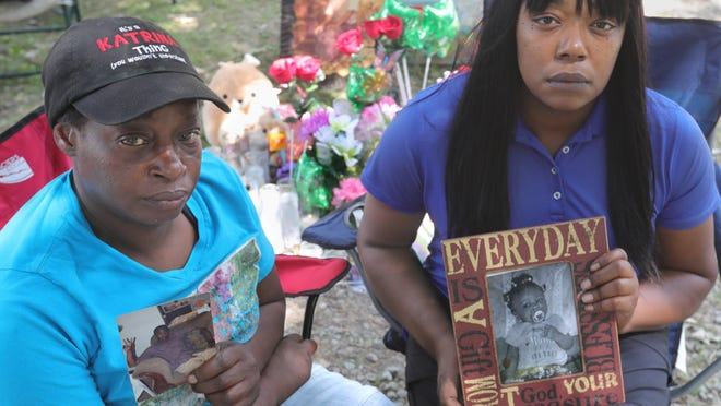 Sisters Katrina Lee, left, and Carmon Lee mourn the death of their brother Horace Lee and his daughter Azeria Tucker on Tuesday in Akron.