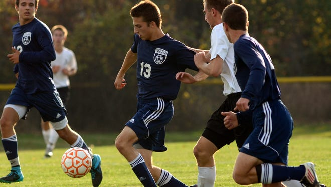 Blue Devils' Brandon VanGorp tries to get by an Almont defender Monday, Oct. 12 during high school soccer action at Almont.