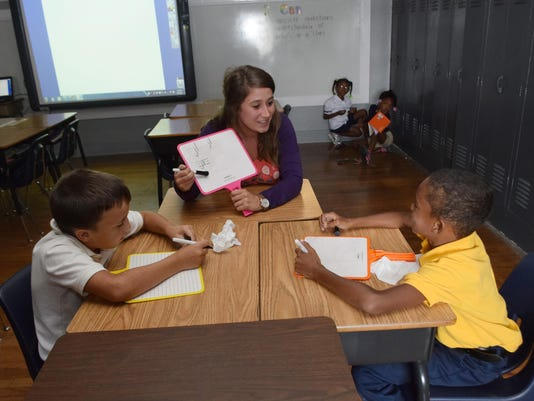 ANI Jennifer Kirkikis Jennifer Kirkikis (center) is a second-grade teacher at D.F. Huddle Elementary School in Alexandria. Here she helps two of her students Jaxon Thompson (left) and Kendall Williams with reading. -Melinda Martinez/The Town Talk