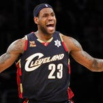 LeBron James reacts during the second half of a 2009 Cleveland Cavaliers game against the Los Angeles Lakers. James told Sports Illustrated on Friday he is leaving the Miami Heat to return to the Cavs.