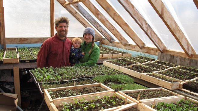 Edge Fuentes stands with his wife, Katie Spring, and their 9-month-old son, Waylon, in their planting room surrounded by seedlings for vegetables and flowers at their Good Heart Farmstead  in Worcester, Vt. Spring and Fuentes back the GMO labeling bill passed by the Vermont Legislature. They believe people need to be able to know what's in their food.