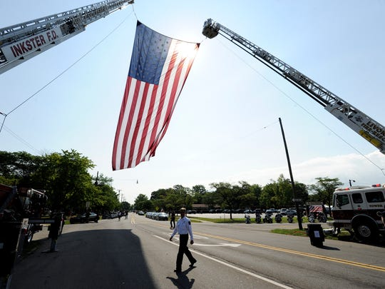 A 30-foot by 60-foot U.S. flag flies from Inkster's FD Ladder 6, left, and Livonia's FD Tower 1.