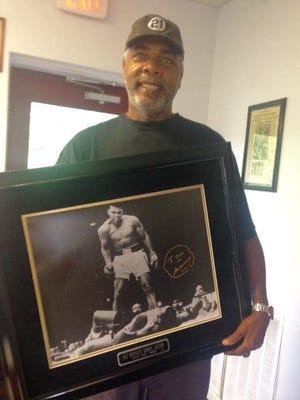 Former Reds outfielder Dave Parker holds a framed photo Muhammad Ali signed for him of Ali's fight with Sonny Liston.