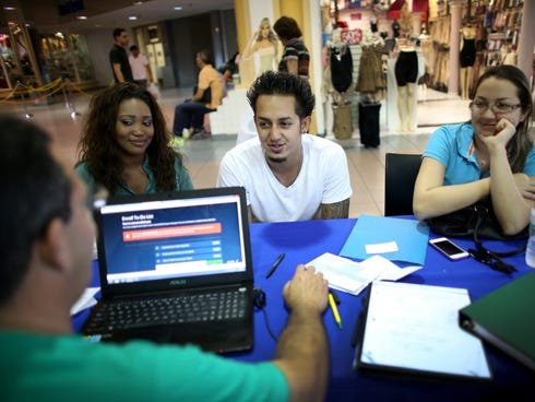 John Riascos, in white shirt, speaks with Mario Ricart, an insurance agent with Sunshine Life and Health Advisors, about purchasing insurance under the Affordable Care Act at a kiosk setup at the Mall of Americas on Dec. 11 in Miami.