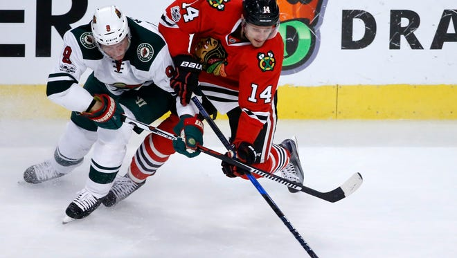 Chicago Blackhawks' Richard Panik (14) and Minnesota Wild's Mikko Koivu battle for the puck during the first period of an NHL hockey game Sunday, March 12, 2017, in Chicago.