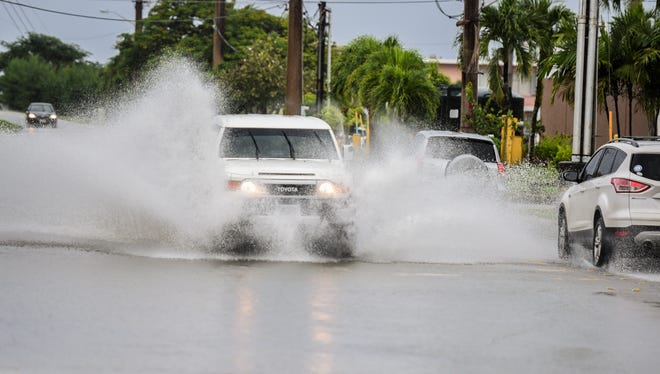 A driver splashes through ponding water, resulting from a passing downpour on Ypao Road, in Tamuning on Tuesday, Oct. 17, 2017.