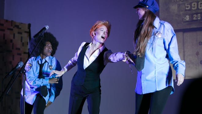 Jill Rittinger (as David Bowie), center, performs in a re-enactment of Bowie's arrest in Rochester in 1976 during Bowieoke at Visual Studies Workshop in Rochester on Oct. 31, 2015.