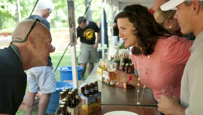 Kevin Elliott talks with Danielle Shockey about beer from Bell's Brewery during the Noblesville Brewfest in Forest Park on Sept. 28, 2013.