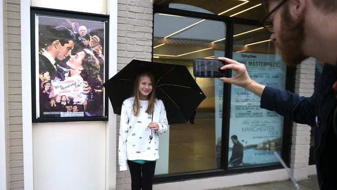 """Drew DeBoard take a photo of his daughter Zilah after seeing the movie """"its a Wonderful Life"""" at the Belcourt Theatre on Christmas Eve ."""