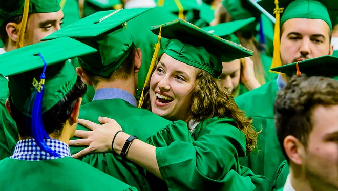 international relations graduate hugs her friend Tyler Lawerence after MSU spring commencement in the spring of 2016.