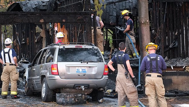 Firefighters clean up after a house fire on Boichot Road in DeWitt Township Monday, Oct. 23, 2017.