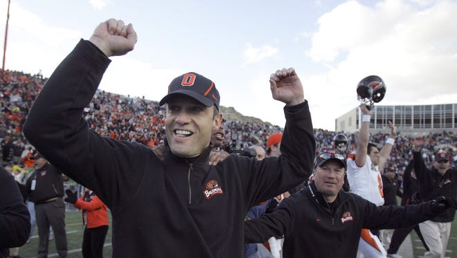 Oregon State coach Mike Riley runs onto the field after Oregon State's 38-39 win over Missouri in the Sun Bowl football game in El Paso, Texas, Friday, Dec. 29, 2006.