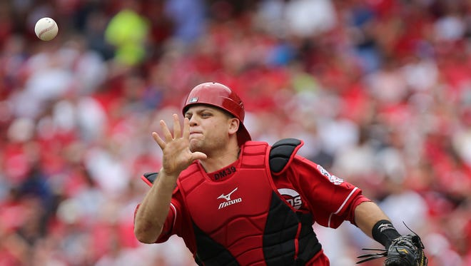 Catcher Devin Mesoraco tosses the ball to third base to tag a runner out in the seventh inning as the Cincinnati Reds take on the Los Angeles Dodgers at Great American Ball Park  on Thursday.