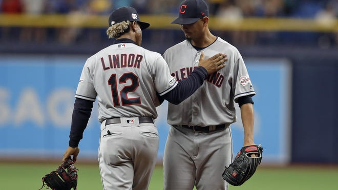 Cleveland Indians shortstop Francisco Lindor (12) pats Indians pitcher Carlos Carrasco on the chest after he warmed up during the seventh inning of a baseball game against the Tampa Bay Rays Sunday, Sept. 1, 2019, in St. Petersburg, Fla. Carrasco is making his first appearance since May, when he was diagnosed with leukemia.