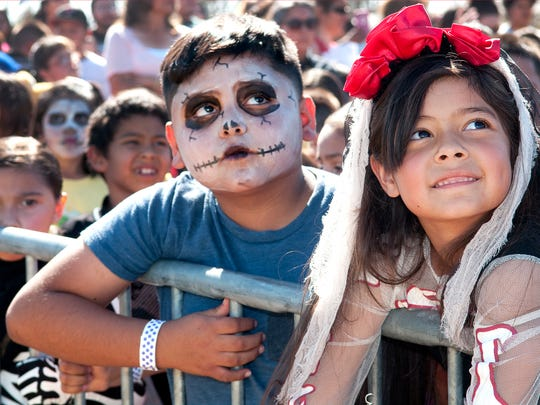 Genisis Meza, 7, (R) and Isaiah Ramirez, 8, (L) have their eyes on the prize, as they watch the cranes from Weaver's Welding drop the candy for the 10th Annual Great Pumpkin Candy Drop Sunday afternoon at Maag Field.