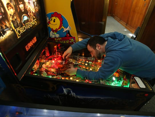 Manager Fil Nobile works on a Lord of the Rings pinball