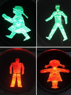 This composite file photo shows a traffic light woman (Ampelfrau), left, and a traffic light man (Ampelmann) in Cologne, Germany, on March 10, 2014.
