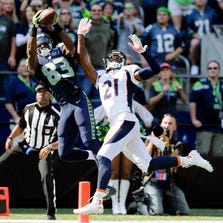 Sep 21, 2014; Seattle, WA, USA; Seattle Seahawks wide receiver Ricardo Lockette (83) catches a touchdown pass over Denver Broncos cornerback Aqib Talib (21) during the first half at CenturyLink Field.