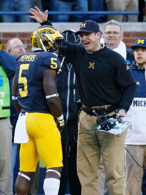 Michigan's Jabrill Peppers (5) celebrates with coach Jim Harbaugh after scoring a touchdown against Rutgers on Nov. 7, 2015, in Ann Arbor.