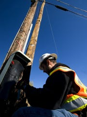 A Fairpoint service technician works on a pedestal box in Charlotte in 2009.